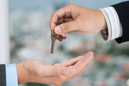 Real estate broker giving the key to the client Stock Photo