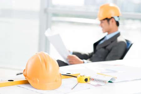 supervisión: Imagen de un contratista que trabaja con un casco de seguridad y herramientas de medición en el primer plano