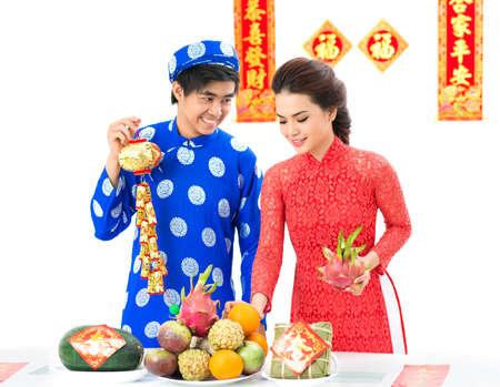 rice cake: Vietnamese couple decorating festive table for Tet Stock Photo