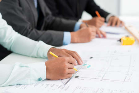 occupied: Close-up image of architects being occupied with paperwork