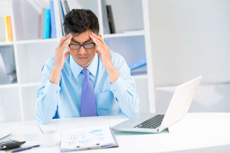 Young business worker suffering from a headache after a long working day