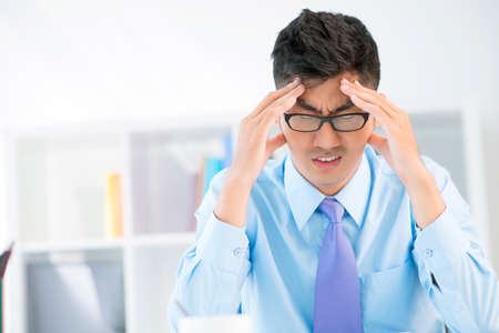 overworking: Portrait of a stressed manager in office