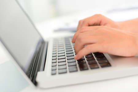 peripherals: Close-up of female hands typing on the laptop keyboard