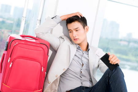 Portrait of young businessman with luggage touching his head in trouble Stock Photo