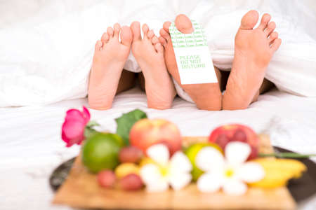 footcare: Image of two pairs of bare feet of man and woman lying under blanket with low calorie breakfast in front
