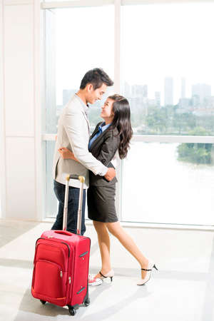 Portrait of young happy couple with baggage looking at one another in airport