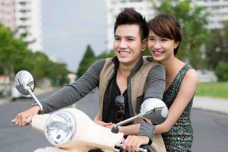 Girl and guy enjoying an urban scooter ride Stock Photo