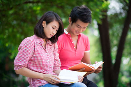 Two students reading for seminar outdoors