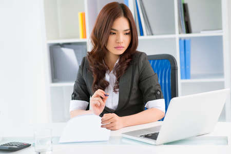 lovely businesswoman: Lovely businesswoman taking a look at digital data displayed on the laptop screen