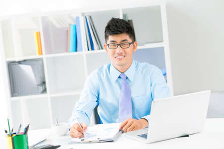 analyst: Portrait of a young successful analyst being occupied with paperwork