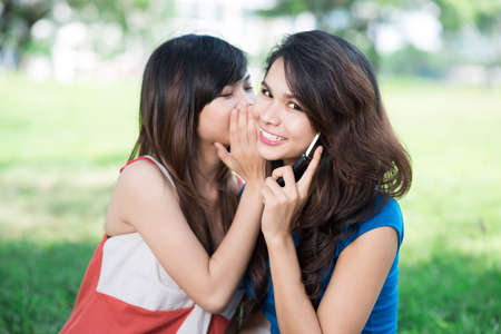Image of a teenage girl sharing secret with her friend who talks over the phone Stock Photo