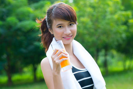 maintain: Portrait of a lovely girl drinking orange juice to maintain vitality