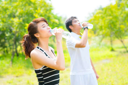 sediento: Thirsty athletes drinking cool water after the workout