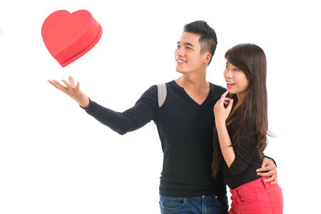 Young man levitating a heart-shaped gift-box to amaze his girlfriend