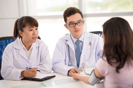Handsome physician and his nurse diagnosing a young female patient  Imagens
