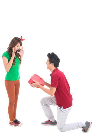 heartshaped: Isolated image of a guy presenting his girlfriend with a heart-shaped giftbox, conceptual shot, good for Valentine's Day