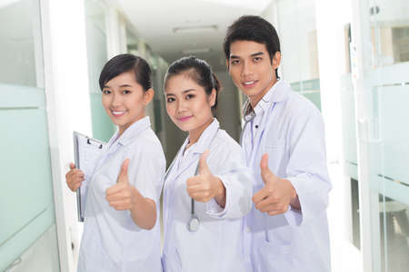 thumbup: Your health is in the hands of enthusiastic clinicians with their thumbs up Stock Photo
