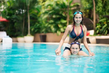Girl sitting on her boyfriend's shoulders in a swimming pool