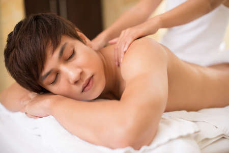 niño sin camisa: Relaxed guy receiving spa treatment which relieves shoulder tension