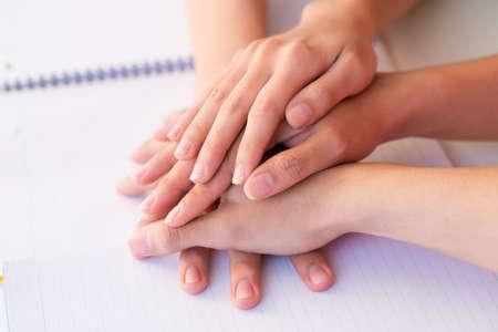 manos unidas: Pila de manos en libro Foto de archivo