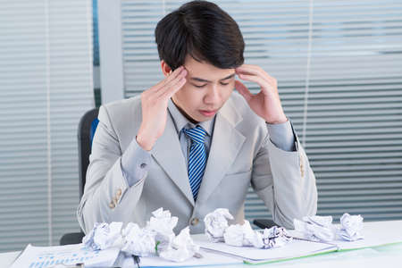 Unhappy manager suffering from headache after long working hours Stock Photo