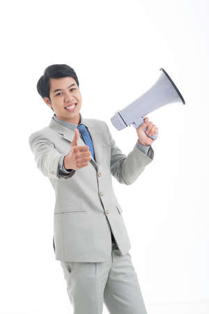 Cheerful office guy with megaphone holding his thumb up