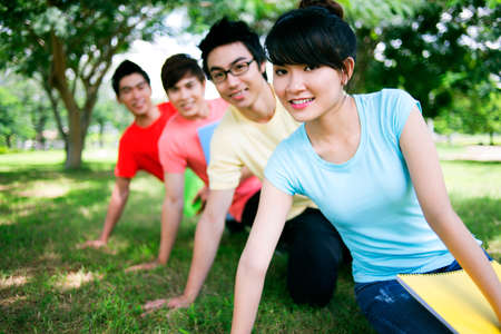 Four cheerful students sitting on grass in a row