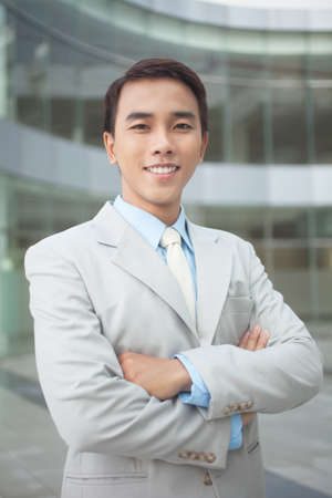 promising: Vertical image of a promising business worker looking at the camera with a confident smile Stock Photo