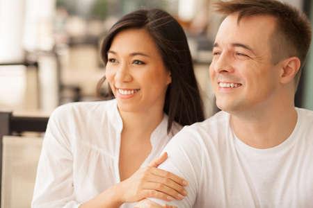 pareja de esposos: Pareja de jóvenes sentados juntos y mirando a otro lado Foto de archivo
