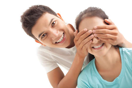 covering eyes: Smiling boy covering eyes of his girlfriend