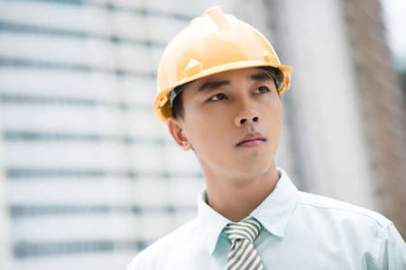 Portrait of a young man in formalwear wearing hardhat  Stock Photo