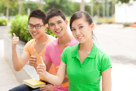 vietnamese ethnicity: Three students showing thumbs outdoors