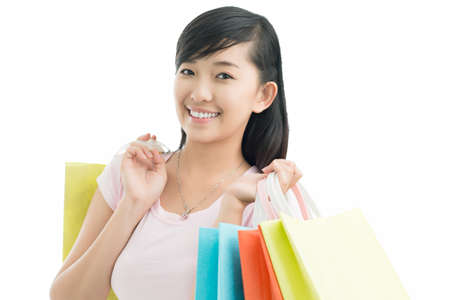 Portrait of a girl with shopping bags looking at camera and smiling