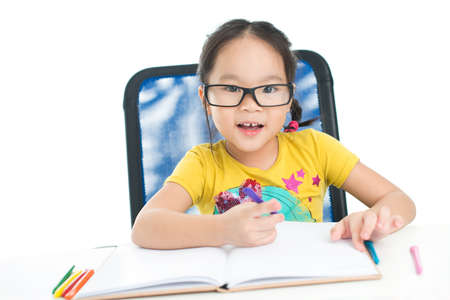 Prodigy: Cute little girl wearing big eyeglasses doing homework Zdjęcie Seryjne