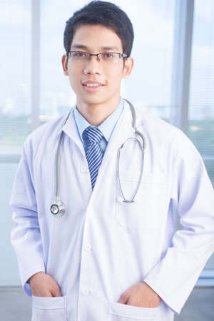 clinician: Portrait of smiling male clinician with stethoscope looking at camera in hospital