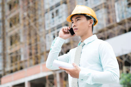 clarify: Young project manager calling by phone to clarify important details