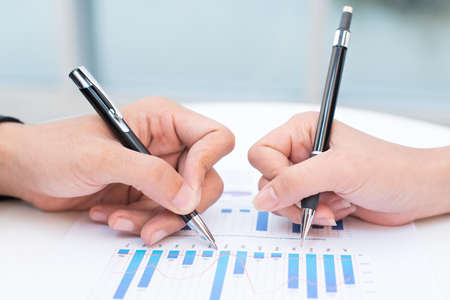 Close-up of a business documents with graphs analyzed by business people Stock Photo