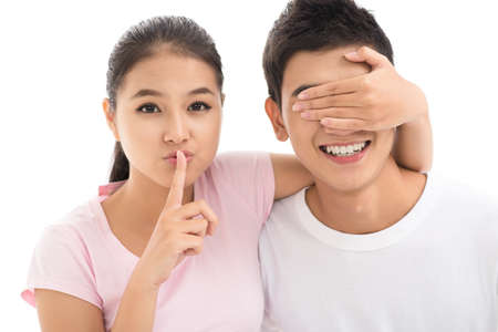Girl keeping her identity in secret covering the guy?s eyes and making a shush gesture