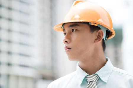 prospection: Close-up portrait of a young businessman in hardhat looking in future with confidence