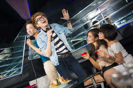 funny guys: Funny guys singing karaoke to entertain their female friends Stock Photo