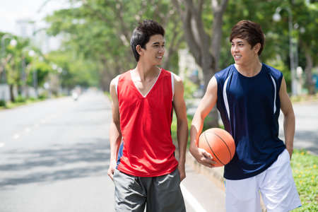 Two young talking basketball players walking in the park Stock Photo