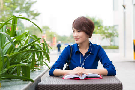 audio book: Portrait of a woman at a cafe with a book and headphones Stock Photo