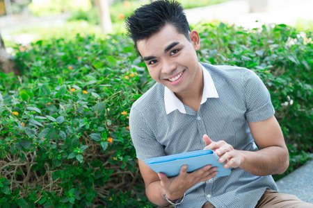 Pretty guy with touchpad outdoors looking at camera