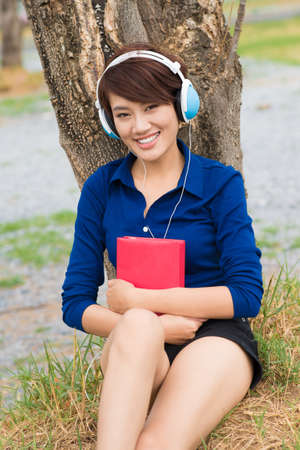 audio book: Portrait of a young girl in headphones sitting and looking at camera Stock Photo