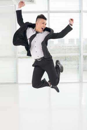 Vertical image of a jumping young asian businessman