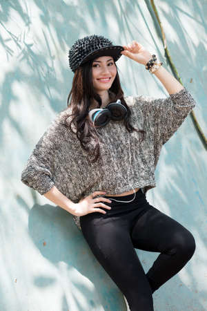 rapping: Vertical portrait of a smiling hipster girl leaning against the wall outside Stock Photo