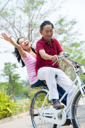 Portrait of a senior couple bicycling in the park Stock Photo