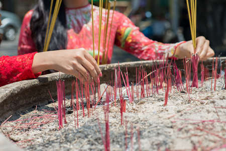 Close-up of female hands with incense sticks