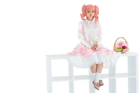 shelve: Isolated image of a kawaii girl sitting on a white shelve stand and pouting her lips