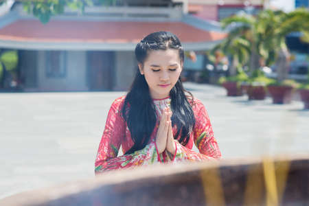 Image of a buddhist woman praying in the temple